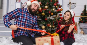 father and daughter with presents in front of Christmas tree